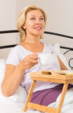 Mature woman enjoying breakfast in bed Stock Images