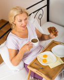 Mature woman enjoying breakfast in bed Stock Photography