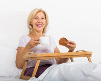 Mature woman enjoying breakfast in bed Royalty Free Stock Photo