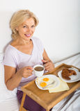 Mature woman enjoying breakfast in bed Royalty Free Stock Photos