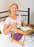 Mature woman enjoying breakfast in bed Stock Photo