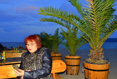 Mature woman enjoying cellphone. Relaxing mature woman enjoying cell phone at beach restaurant .Picture taken on May 15,2014 at Varna,Bulgaria.pace with edge Stock Photo