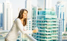 Woman on a highrise balcony. Mature woman is enjoying city view from her balcony in highrise building Stock Photos