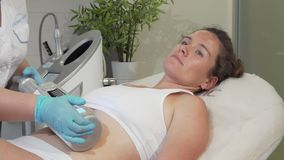 Mature woman enjoying endospheres hardware massage at beauty clinic. Happy woman smiling to the camera, receiving endospheres therapy treatment by beautician stock footage