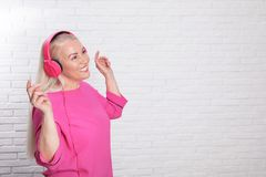 Mature woman enjoying music in headphones against brick wall royalty free stock photo