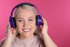 Mature woman enjoying music in headphones royalty free stock image