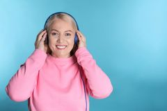 Mature woman enjoying music in headphones on color background stock photography