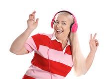 Mature woman enjoying music in headphones stock images