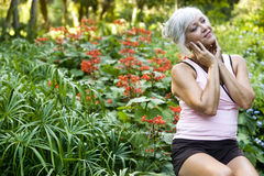 Mature woman enjoying park foliage Royalty Free Stock Image