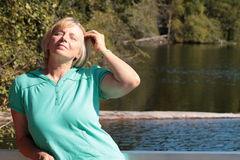 Mature woman enjoying the sun in nature Royalty Free Stock Image
