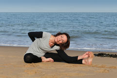 Mature woman enjoying yoga on the beach. Mature woman doing head-to-knee yoga pose on the beach Royalty Free Stock Photos