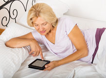Mature woman with ereader laying on bed Stock Photos