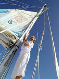Mature woman erecting sail on boat, smiling, portrait, low angle view Royalty Free Stock Photography
