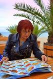 Mature woman examines menu. Mature woman looking at beach restaurant menu.Picture taken on May 15,2014 at Varna,Bulgaria royalty free stock photo