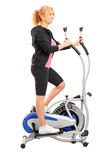 Mature woman excersing on a cross trainer Royalty Free Stock Image