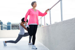 Mature woman exercising with female friend Royalty Free Stock Photos