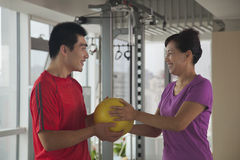 Mature woman exercising with her trainer stock photography
