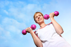 Mature woman exercising outdoors Stock Photos