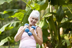 Mature woman exercising in park with hand weights Royalty Free Stock Images