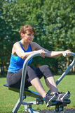 Mature Woman Exercising On Rowing Machine In Park Stock Image