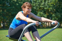 Mature Woman Exercising On Rowing Machine In Park Stock Images