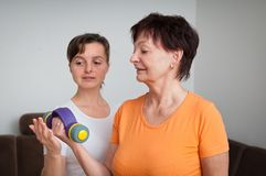 Mature woman exercising with trainer Royalty Free Stock Photo