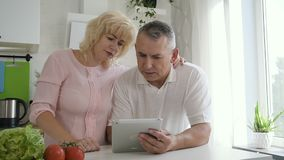Mature woman explaining senior husband how to use tablet computer. Aged man sitting at the counter in cozy kitchen and hodling digital device. Wife hugging him stock video footage