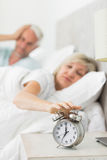 Mature woman extending hand to alarm clock in bed Royalty Free Stock Photography