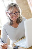 Mature woman with eyeglasses using laptop Stock Photos