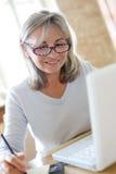 Mature woman with eyeglasses using laptop Stock Photos