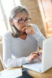Mature woman with eyeglasses working from home Stock Photo