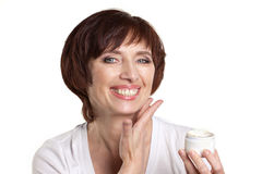 Mature woman with facial cream Stock Images