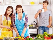 Mature woman with family preparing at kitchen. Royalty Free Stock Images