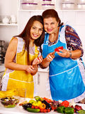 Mature woman with family preparing at kitchen. Stock Photo