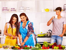 Mature woman with family preparing at kitchen. Royalty Free Stock Photography