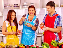Mature woman with family preparing at kitchen royalty free stock image