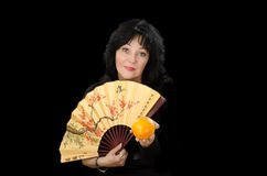 Mature woman with fan offering a orange to you Stock Photography
