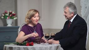 Mature woman feeding man with grapes at restaurant stock video footage