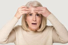Mature woman feels upset about facial wrinkles studio conceptual image stock photography
