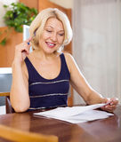 Mature woman filling in paper Royalty Free Stock Image