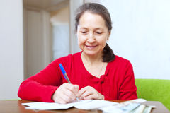 Mature woman fills in  documents Stock Photo