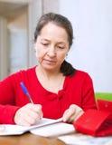 Mature woman fills utility bills Royalty Free Stock Image