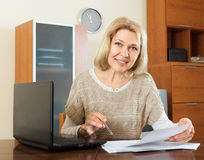 Mature woman with financial documents at table Royalty Free Stock Image