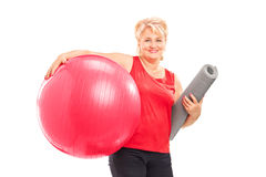Mature woman with a fitness ball and an exercise mat Royalty Free Stock Images