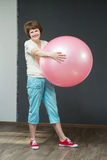 Mature woman with fitness ball. Smiling fit aged lady with exercise ball Royalty Free Stock Photography