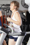 Mature woman at fitness centre. Mature woman running on tradmill at fitness centre Royalty Free Stock Image