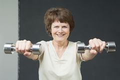 Mature woman with fitness dumbbells Stock Image