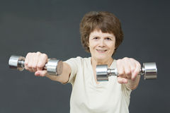 Mature woman with fitness dumbbells Stock Photography