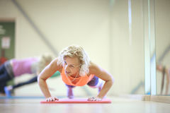 Mature woman fitness trainer pushing-up Stock Photo