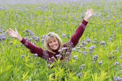 Mature woman in flower field Royalty Free Stock Image